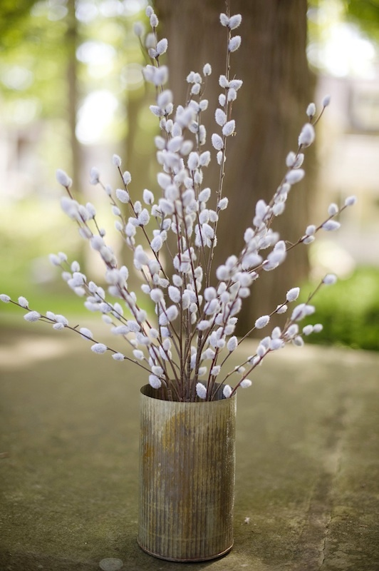 a rough metal vase with willow is a cute decoration or centerpiece for a modern or rustic spring home