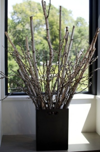 a black square planter with branches and willow that refreshes the natural arrangement for spring and makes it bolder