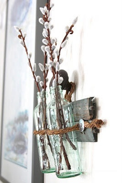 a reclaimed wooden shelf on the wall, glass bottles and willow branches for spring home decor