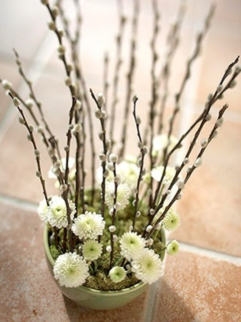 a grene planter with moss, neutral blooms and willow is a cool spring centerpiece or decoration