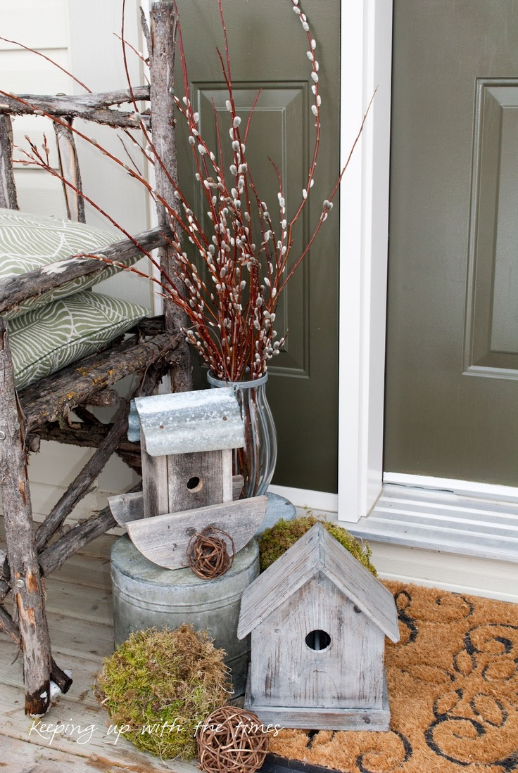 some wooden bird houses, a bucket, a moss and vine ball and some willow in an elegant vase for outdoor or front porch decor