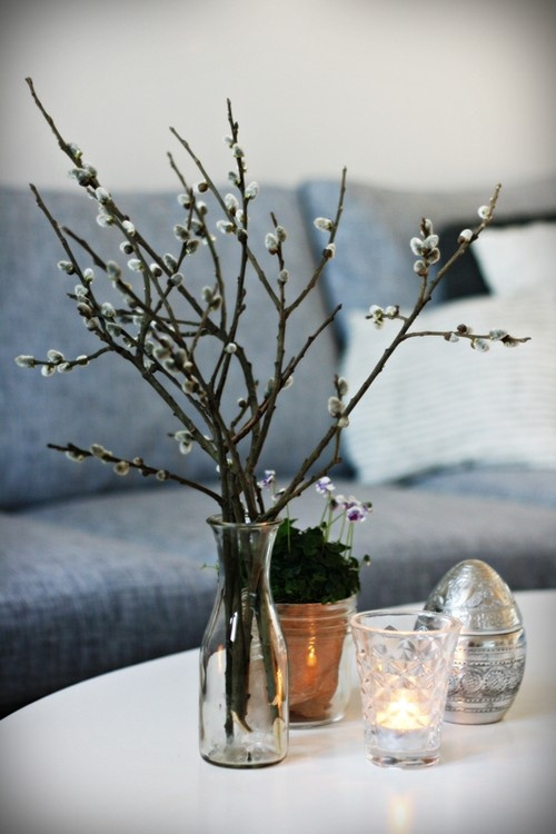 a clear glass vase with willow, some blooms in a pot and a large silver egg for natural and simple spring decor