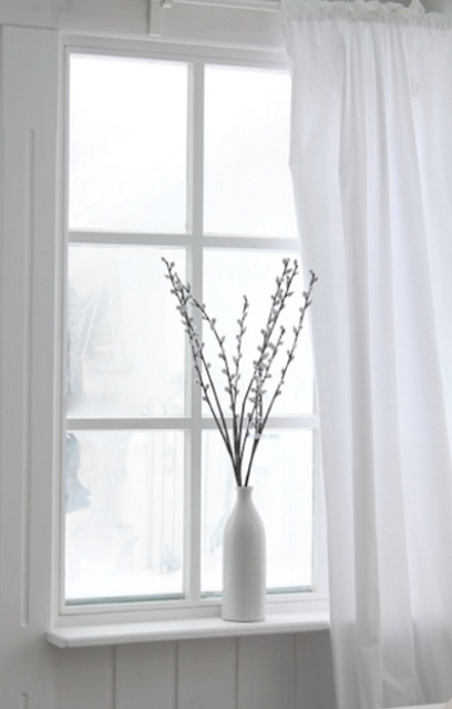 a white porcelain vase with willow is a cool idea for decorating your windowsills