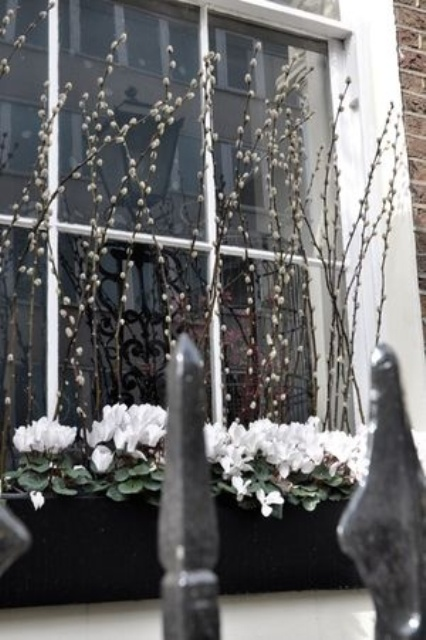 window boxes with white blooms and willow is a cool idea to style your home for spring outdoors