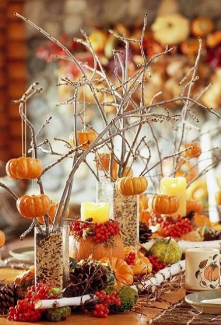 cute fall centerpiece of branches put into glasses with some filler and pumpkins hanging on them