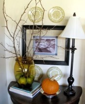 fall decor wiht a single pumpkin on a plate and some branches in a clear green vase plus apples inside it