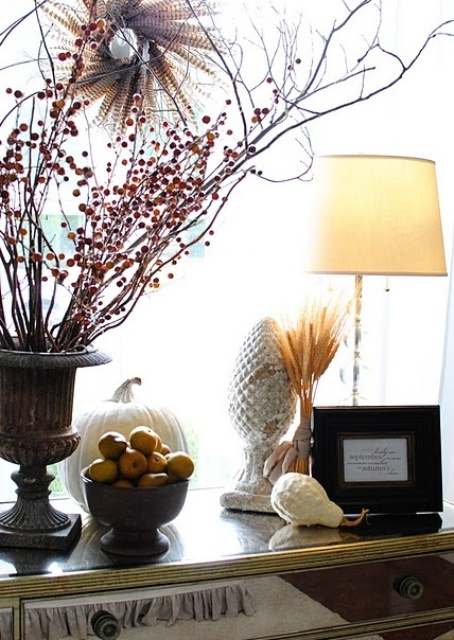 a fall arrangement with branches and berries in a vintage urn, pears in a bowl and some wheat