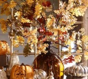 a fall branches with leaves arrangement in a large amber vase plus some faux pumpkins around is a timeless idea for seasonal home decor
