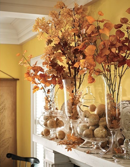 tall clear vases with fall leaf arrangements and clear jars with faux pumpkins and pears for a timeless fall mantel