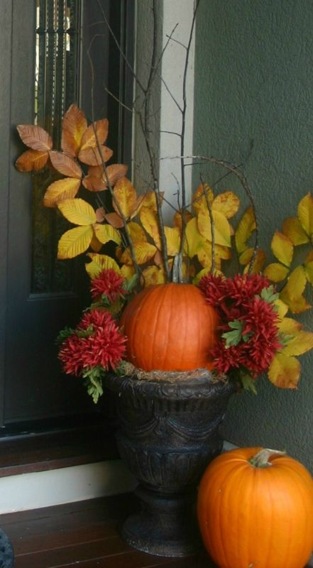 a large vintage urn with hay, pumpkins, blooms and fall leaves on branches for decorating your front porch