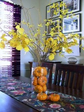a stylish and simple fall centerpiece of a clear vase filled with orange pumpkins and branches with yellow leaves