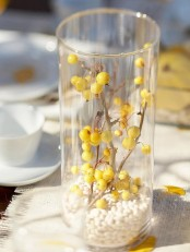 a fall centerpiece of a clear vase filled with white beads and with branches with yellow berries inside