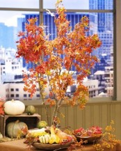 a bold fall decoration of branches with bright red leaves and pumpkins around is super stylish fall idea