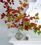 an arrangement of branches with bright fall leaves in a clear vase is a timeless decoraiton that can be created in no time