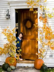 oversized natural pumpkins with tall fall branches inserted into them is a cool outdoor decoration to frame your door