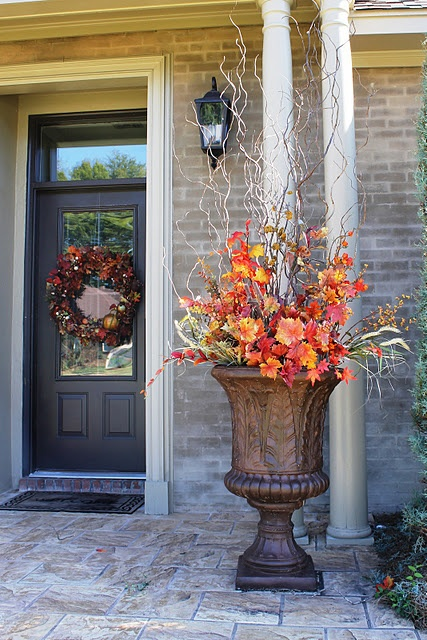 a vintage urn with bright faux leaves and blooms plus some branches is a timeless outdoor fall decoration