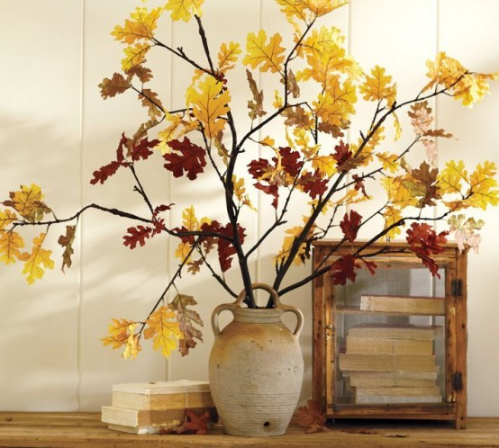 an antique-inspired vase with branches and yellow leaves on them for bold fall decor