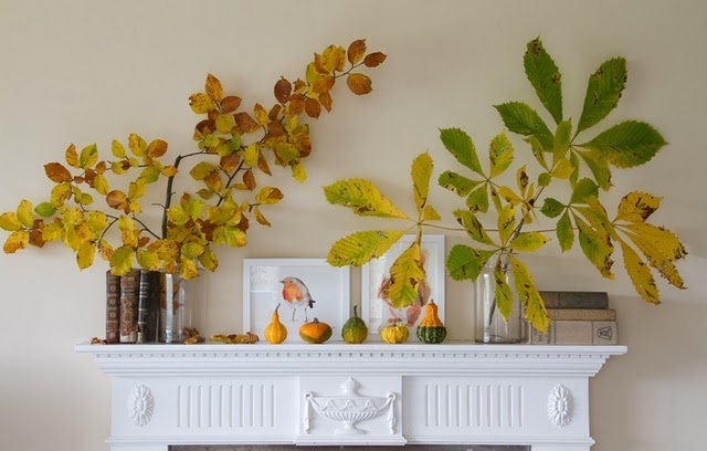 a cool fall mantel with fake fruits and pumpkins and branch and leaf arrangements for a touch of color