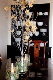 clear vases filled with moss and grass and with branches with fake gold leaves attached to them