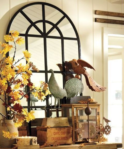 a vase with bright fall leaf branches and fake birds for vintage inspired and elegant fall decor