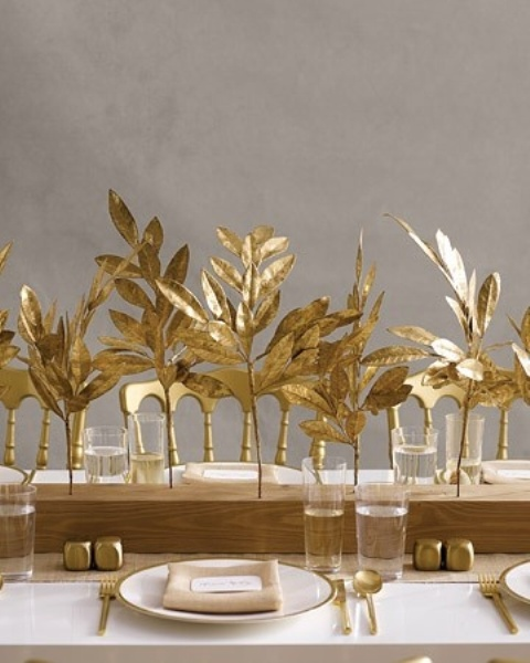 a centerpiece of a wooden slab with gold leaves inserted match the gold cutlery and spruce up the fall tablescape