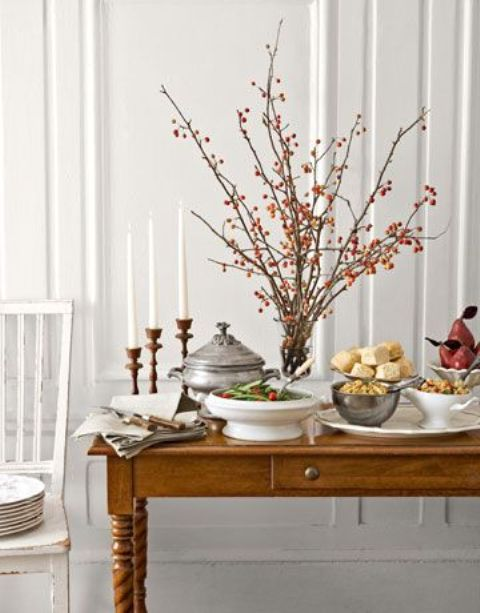 an arrangement of branches with bright red berries as a fall decoration or a centerpiece