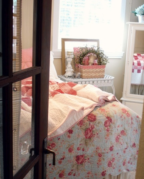 a shabby chic spring bedroom with bright floral and botanical print bedding, a greenery wreath and a bold basket