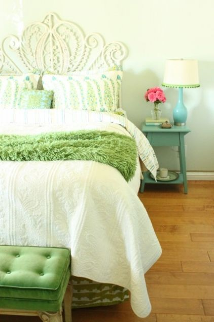 a colorful spring bedroom with botanical prints, a green blanket and a blue lamp