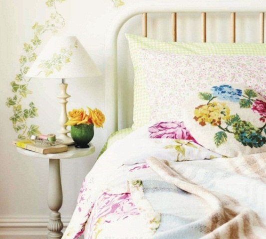 bright floral bedding and botanical print wallpaper and a lamp make the bedroom feel bright and inspired
