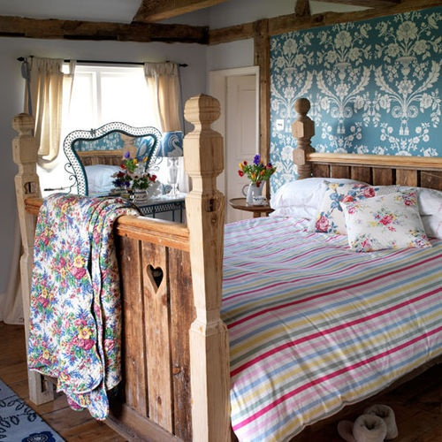 a bright bedroom with floral bedding, a striped blanket, a statement wall and a carved wooden bed feels like rustic spring