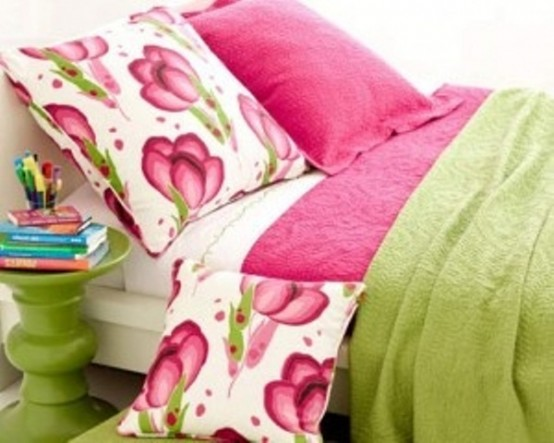 bright bright pink bedding and a side table make the bedroom look bold, bright and fun
