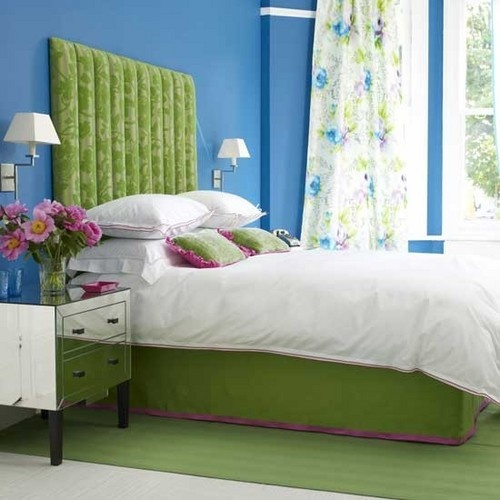 a bright bedroom with bold blue walls, a neon green bed and rug and floral curtains feels very bold and spring-summer