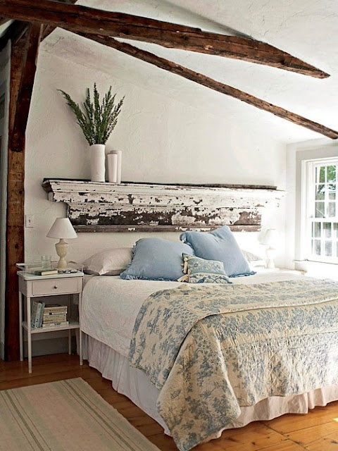a shabby chic bedroom with blue and white bedding and greenery in a vase that make it spring-fresh