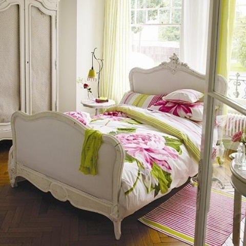 an elegant bedroom with bright green and pink touches, with floral patterns make the space feel veyr bold and spring like