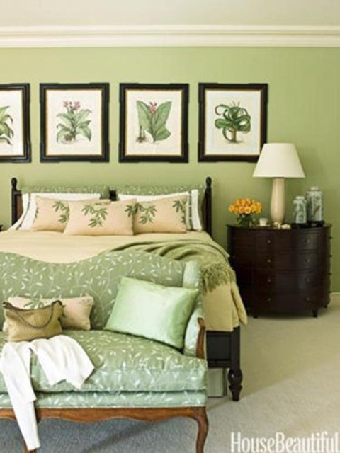 a green bedroom with a gallery wall of botanicals and bright bedding and pillows for a spring feel