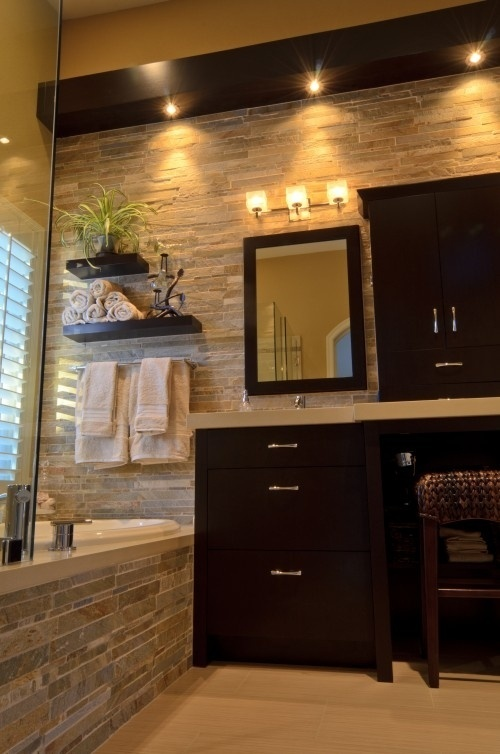 a modern bathroom done with decorative stone and dark furniture plus lights for a contrasting and bold look
