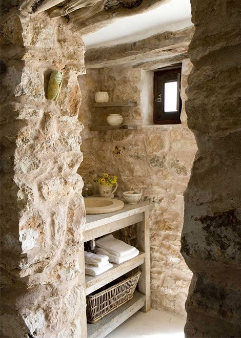 a farmhouse bathroom fully clad with real stone and with a wooden vanity plus floating shelves