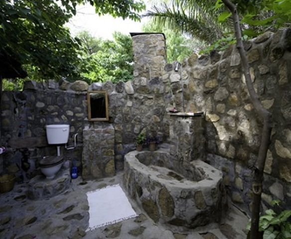 an outdoor bathroom fully made of stone is a cool idea to feel closer to nature and more outdoorsy