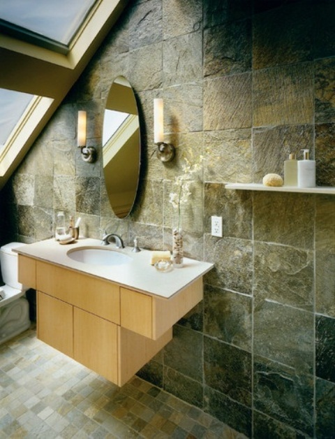 a chic attic bathroom with stone tiles on the wall and tiles on the floor plus a large attic window