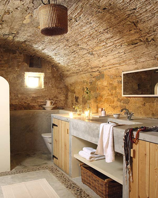 a wabi sabi bathroom with stone walls, concrete and wood furniture and a wicker lampshade